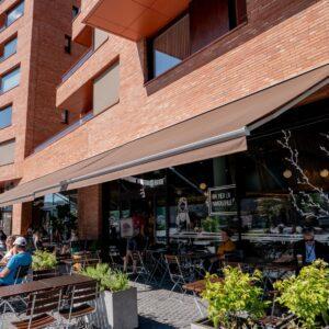 Trivelig kafé med uteservering i første etasje. Store terrassemarkiser med automatisert motorisering. Modelltype er