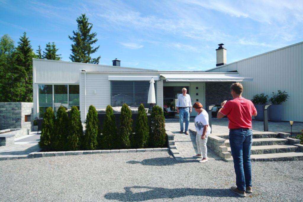 Persienner og terrassemarkise på hvitt hus