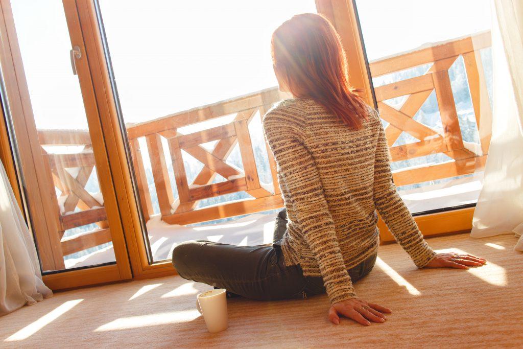 Dame som sitter i sola innenfor vinduene